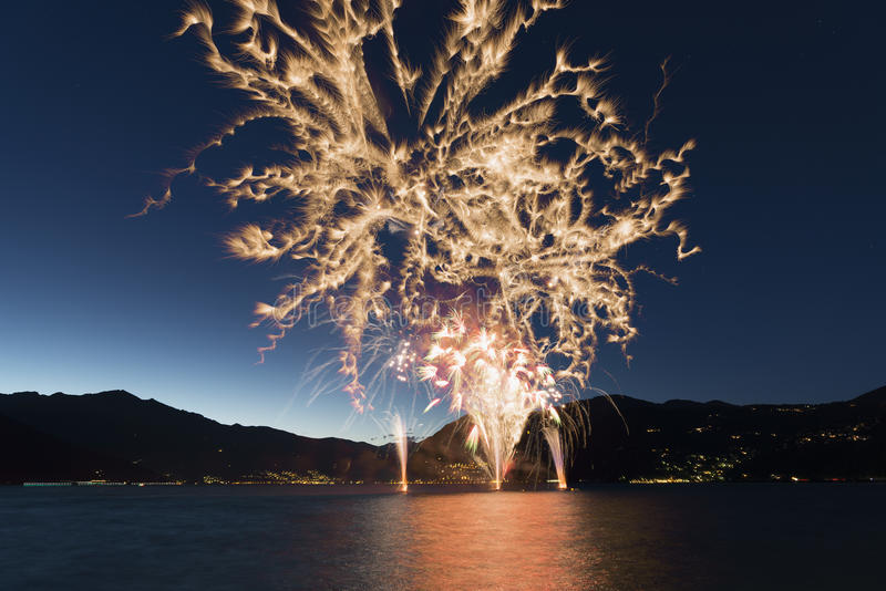 Fireworks on the Lake Maggiore in a summer night. Fireworks on the lakefront of Luino over the Maggiore Lake in a summer evening with blue sky and mountains in stock image