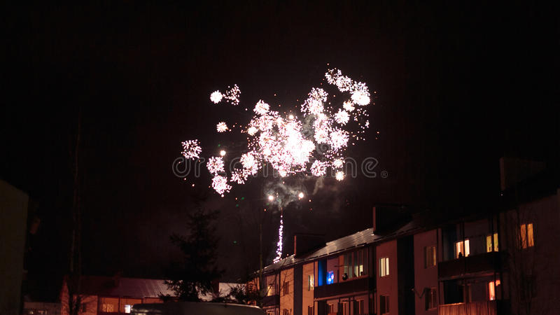 Fireworks in the night sky over houses. New Year`s fireworks in the night sky over houses royalty free stock photos