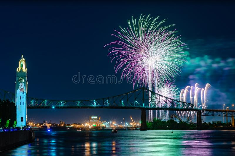 Fireworks over city bridge in Montreal. Fireworks display over jacques cartier bridge in Montreal during international fireworks festival royalty free stock images