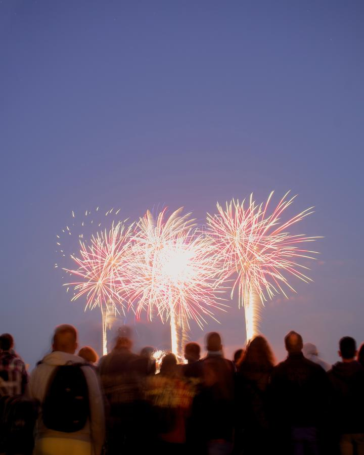 Fireworks with pink sky and people stock photos