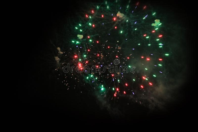 Fireworks. Salute. Sky background Amazing mystery of bright red, green and blue sparkling lights in the night sky during the New. Year and Christmas holidays stock images