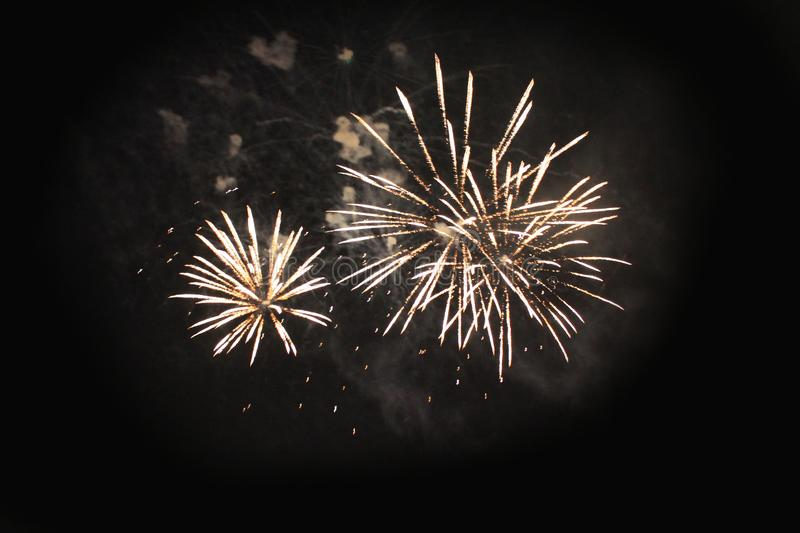 Fireworks. Salute. Sky background Amazing mystery of bright yellow sparkling lights in the night sky during the holiday of New. Year and Christmas royalty free stock photography