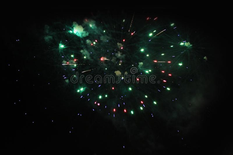 Fireworks. Salute. Sky background The fabulous mystery of bright red, green and blue sparkling lights in the night sky during the. New Year and Christmas royalty free stock images