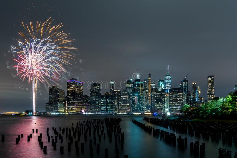 Fireworks and the skyline of New York from Dumbo. A reflection of the city lights and the fireworks seen from the piers of Brooklyn royalty free stock photos