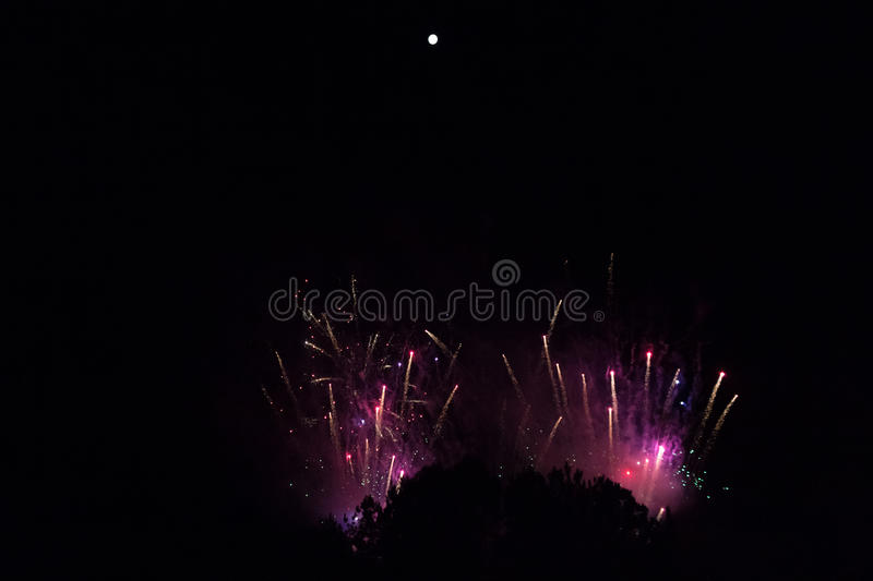 Fireworks in violet and red smoke beneath a bright full moon stock images