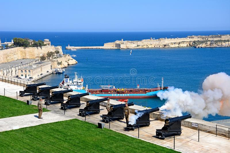 Firing the Noon Gun, Valletta, Malta. Soldiers firing the cannons for the Noon Gun in Upper Barrakka Gardens with views across the Grand Harbour towards Fort stock photo