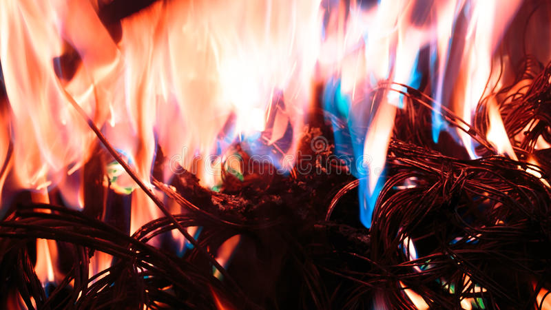 Firing wire in fire. Wires on fire. Firing winding insulation of electrical wiring in the fire close-up royalty free stock photo
