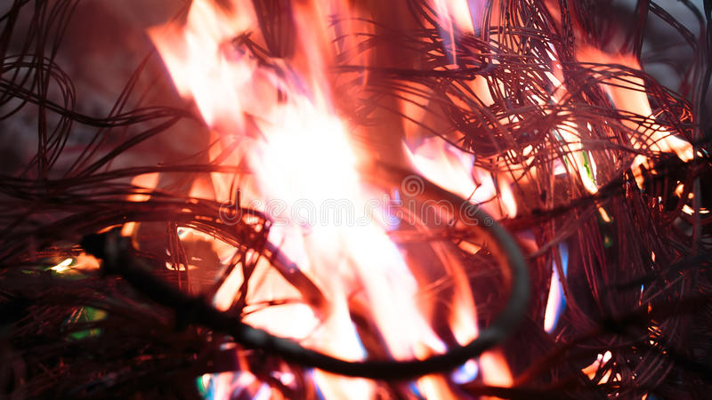 Firing wire in fire. Wires on fire. Firing winding insulation of electrical wiring in the fire close-up royalty free stock photography
