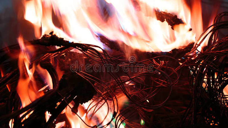 Firing wire in fire. Wires on fire. Firing winding insulation of electrical wiring in the fire close-up royalty free stock photos