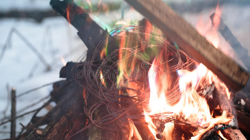Firing wire in fire. Wires on fire. Firing winding insulation of electrical wiring in the fire in the winter woods royalty free stock photos
