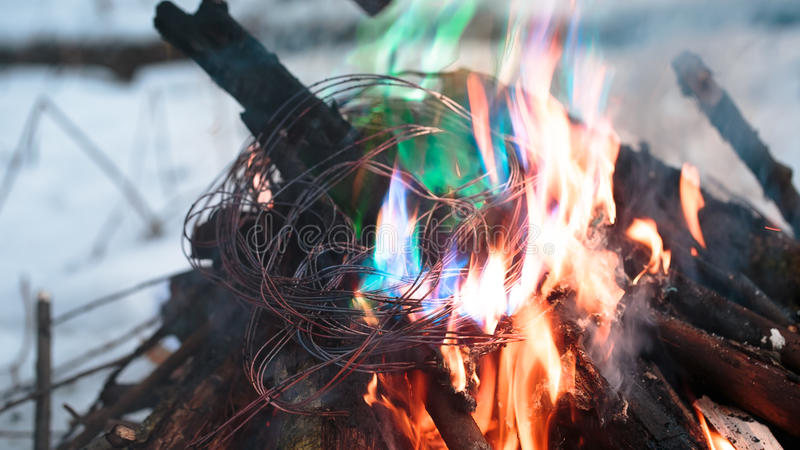 Firing wire in fire. Wires on fire. Firing winding insulation of electrical wiring in the fire in the winter woods royalty free stock photo
