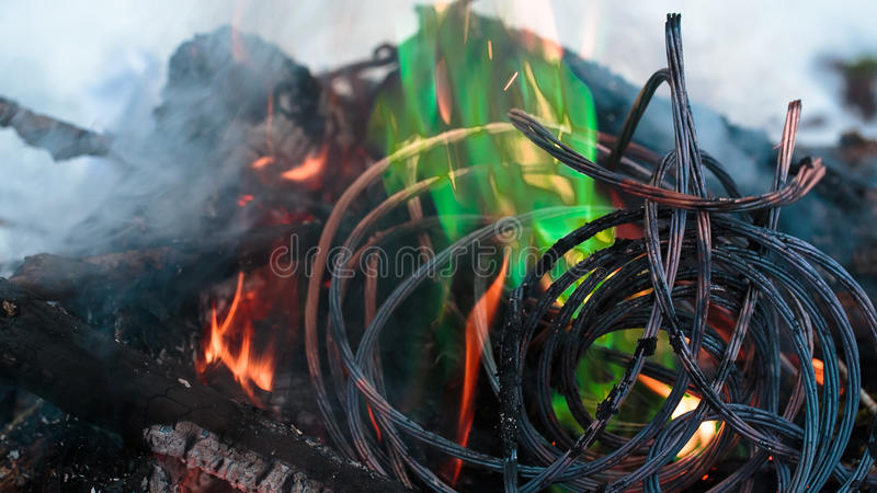 Firing wire in fire. Wires on fire. Firing winding insulation of electrical wiring in the fire in the winter woods stock photo