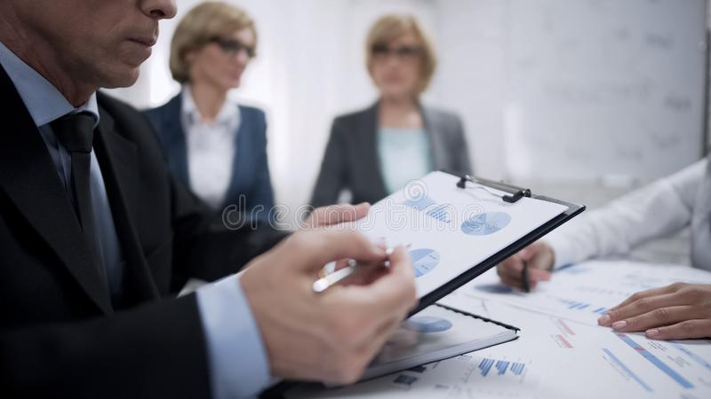 Firm workers studying and analyzing supply and demand statistic on world market stock photos