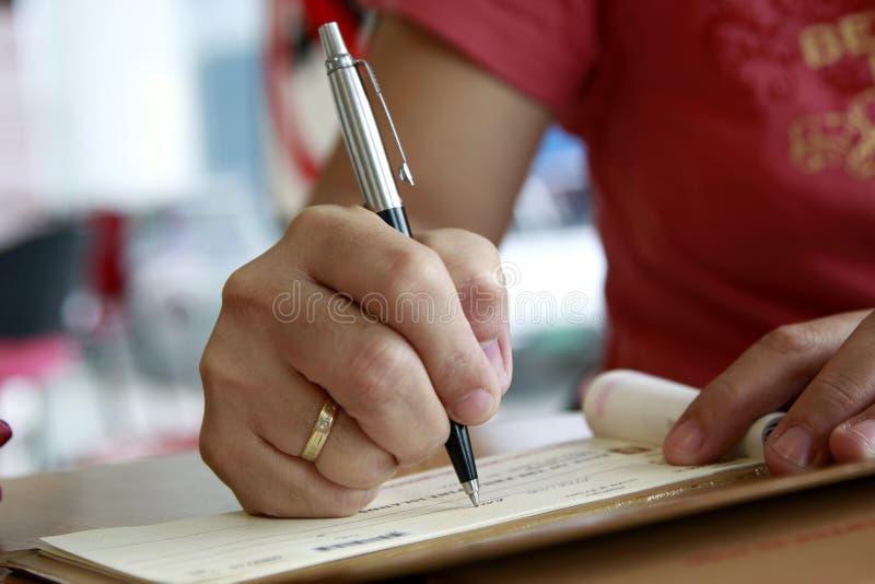 Firma de un cheque de la verificación fotos de archivo