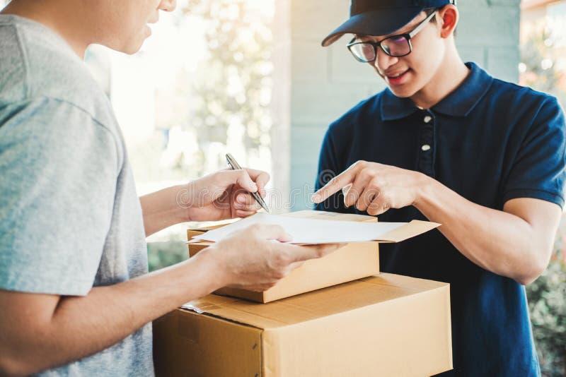Firma dell'uomo del cliente in lavagna per appunti per ricevere pacchetto dal fattorino professionale a casa fotografia stock libera da diritti