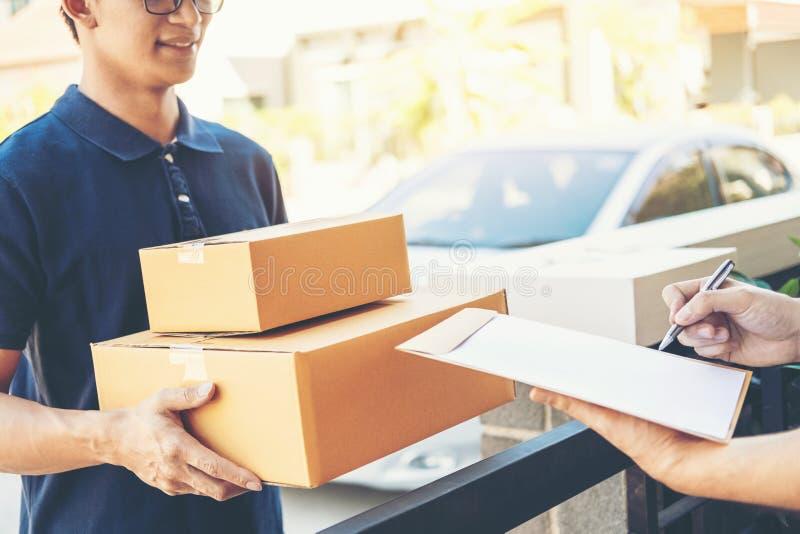 Firma dell'uomo del cliente in lavagna per appunti per ricevere pacchetto dal fattorino professionale a casa immagini stock libere da diritti