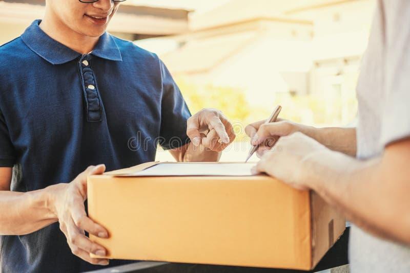 Firma dell'uomo del cliente in lavagna per appunti per ricevere pacchetto dal fattorino professionale a casa fotografia stock