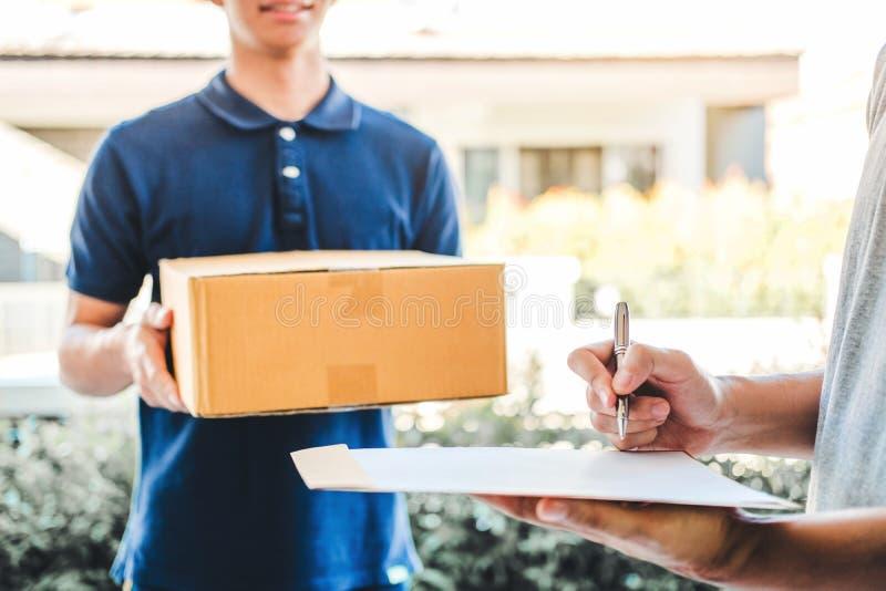 Firma dell'uomo del cliente in lavagna per appunti per ricevere pacchetto dal fattorino professionale a casa immagine stock libera da diritti