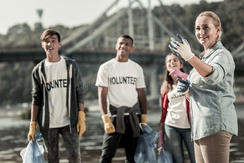 Firma des Teamleiters und drei junger Freiwilliger, die den Strand aufräumen lizenzfreie stockfotos