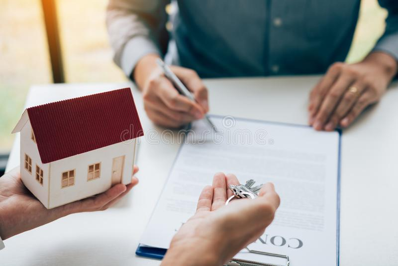 Firma di firma di scrittura del cliente sul contratto di carta con l'agente immobiliare e sulla chiave dare al cliente immagini stock