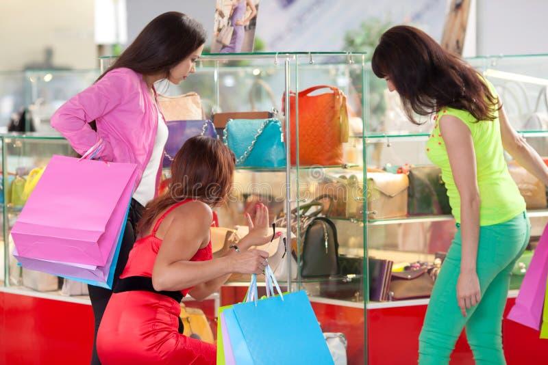 Firma dziewczyny wybiera rzemienne torby na sklepowym okno stoi z powrotem w centrum handlowym zdjęcie royalty free