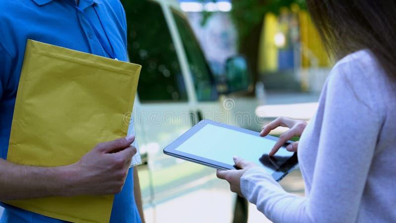 Firma femminile per il pacchetto che riceve in compressa app, tecnologia della società di consegna fotografia stock libera da diritti