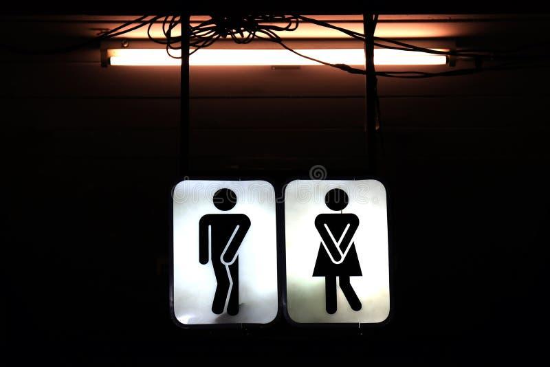 Firma il bagno di notte, il maschio anziano di simbolo della toilette e la femmina nei precedenti di notte fotografia stock