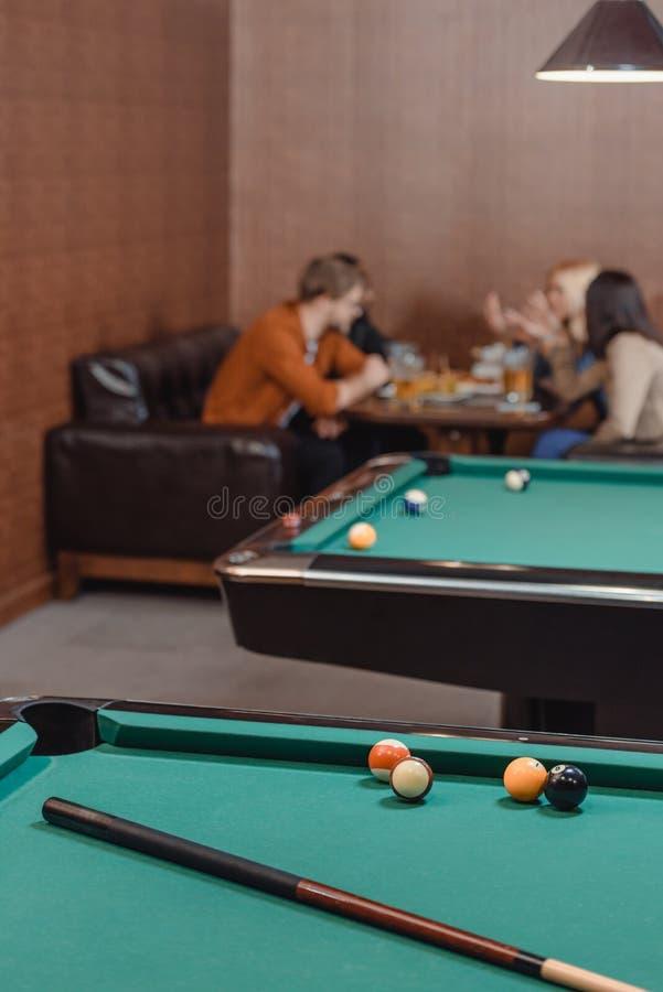 Firma von den multiethnischen Freunden, die neben Billardtisch essen und trinken stockbilder