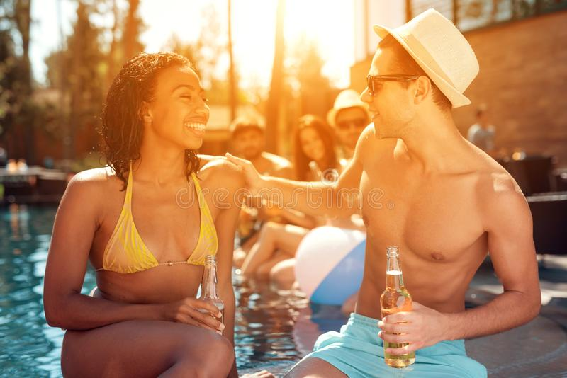 Firma von den sorglosen Freunden wenden Zeitschwimmen im Pool auf Schwimmenpool-party stockfotos