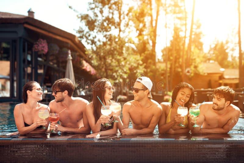 Firma von glücklichen Freunden trinkt Cocktailgetränke im Pool an der Sommerzeit Schwimmenpool-party stockfoto