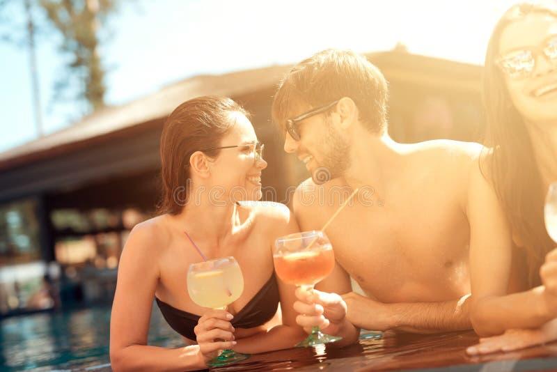 Firma von glücklichen Freunden trinkt Cocktailgetränke im Schwimmbad an der Sommerzeit Schwimmenpool-party lizenzfreies stockbild