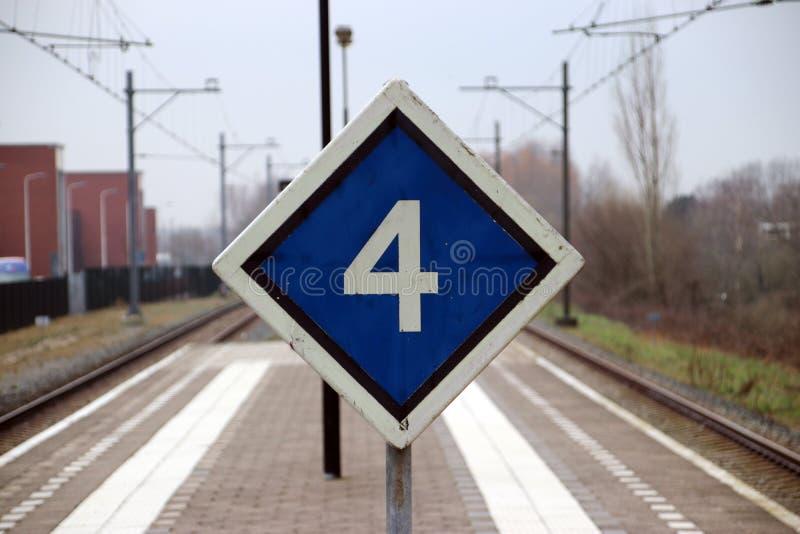 firme con el consejo de la parada para el tren con 4 coches en el medio de 2 p fotografía de archivo