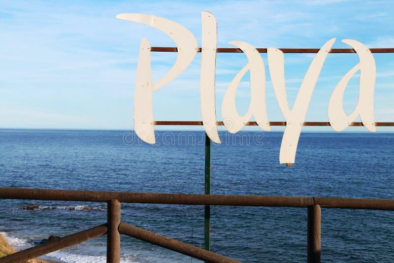 Firme con la playa de la palabra escrita en español: PLAYA foto de archivo