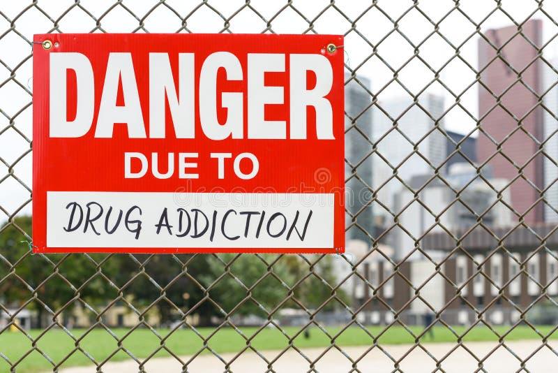 Firme el peligro debido a la ejecución de la drogadicción en la cerca foto de archivo