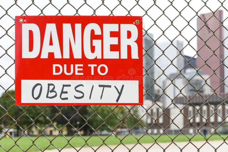 Firme el peligro debido a la ejecución de la obesidad en la cerca fotografía de archivo