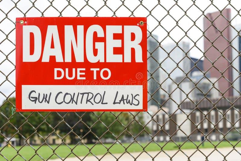 Firme el peligro debido a las leyes de control de armas que cuelgan en la cerca foto de archivo libre de regalías