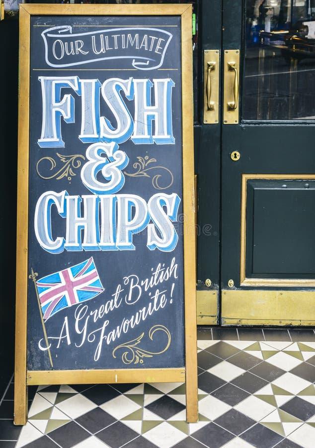 Firme en la pizarra fuera de un pub en Londres que promueve sus últimos pescado frito con patatas fritas, gran favorito británico fotos de archivo