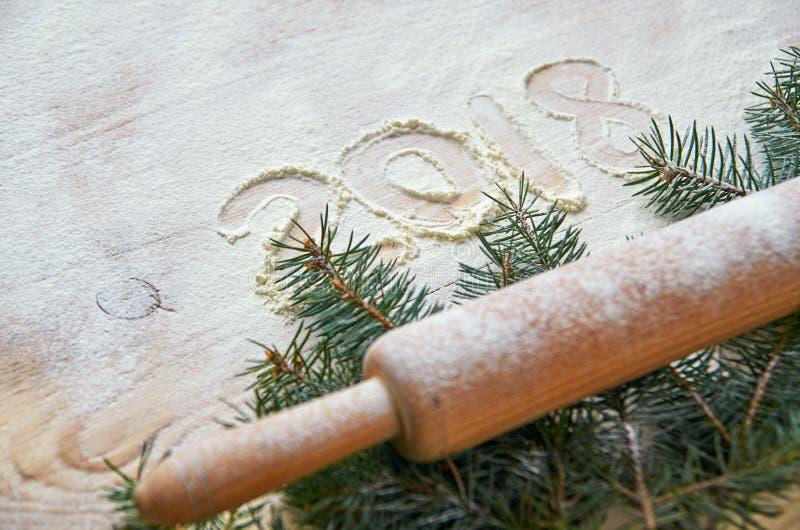 Firme la Feliz Año Nuevo 2018 en la harina en la tabla de madera adornada con la Navidad tres ramas y rodillo pulverizado fotos de archivo libres de regalías