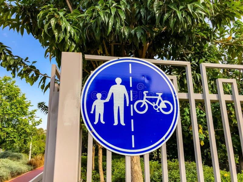 Firme para los peatones y los ciclistas en una cerca blanca cerca de un camino en el parque fotografía de archivo libre de regalías