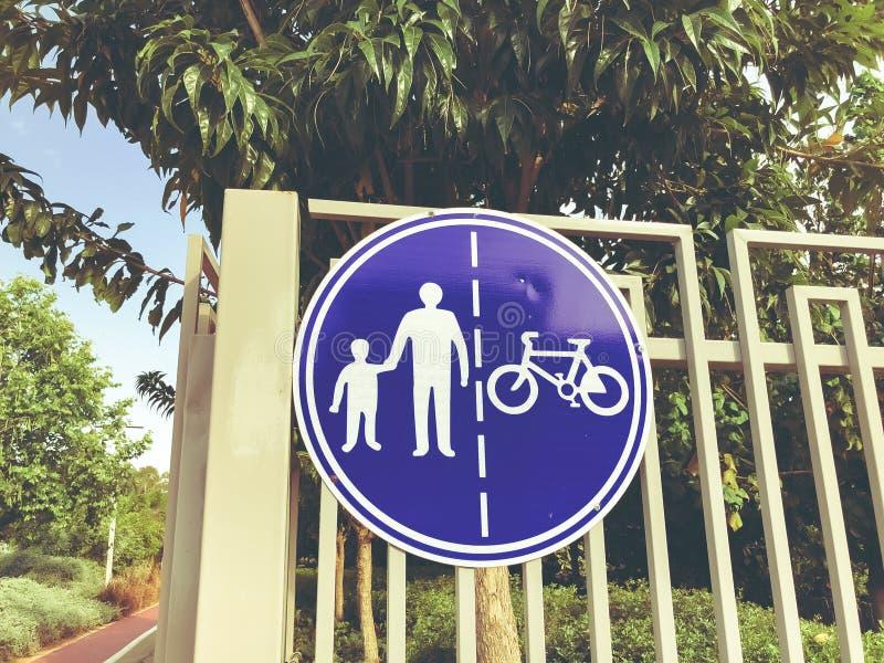 Firme para los peatones y los ciclistas en una cerca blanca cerca de un camino en el parque foto de archivo