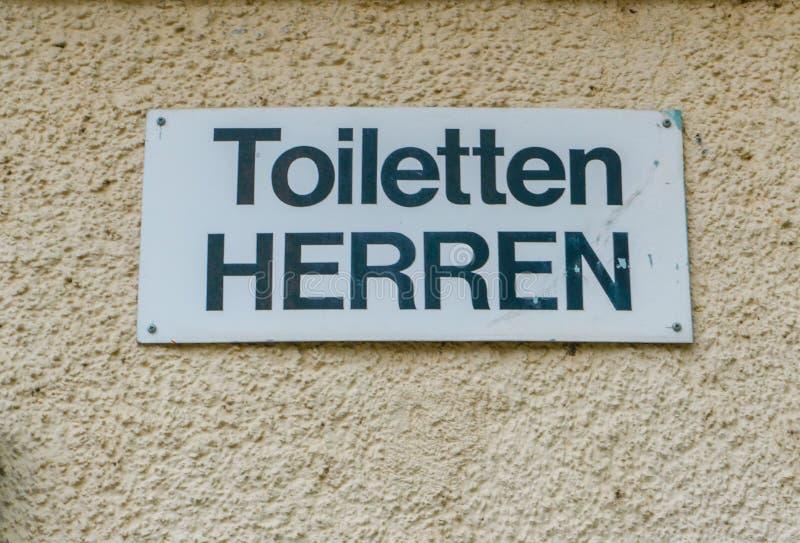 Firme para los retretes públicos para los hombres en lengua alemana imagen de archivo