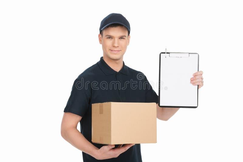 Firme por favor aquí para conseguir su caja. HOL joven alegre del repartidor imagen de archivo