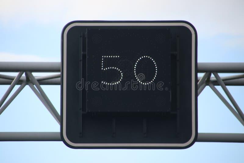 Firme sobre el carril que indica la velocidad obligatoria en kilómetros por imagen de archivo libre de regalías