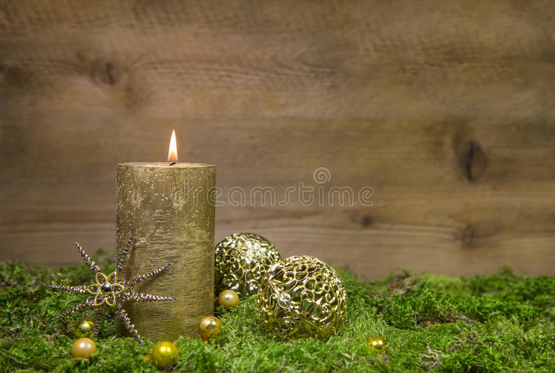 First advent: golden candle burning before wooden background. First advent: golden candle burning before a wooden background stock images