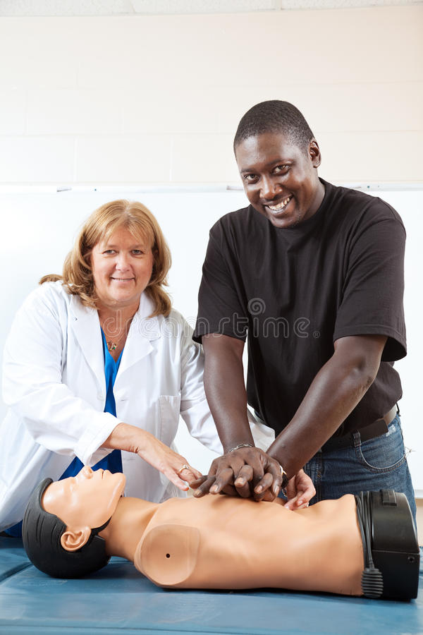 First Aid Classes with Room For Text. Adult first aid or EMT student practicing CPR on a dummy, with the help of a doctor or nurse. Vertical with room for text royalty free stock photography