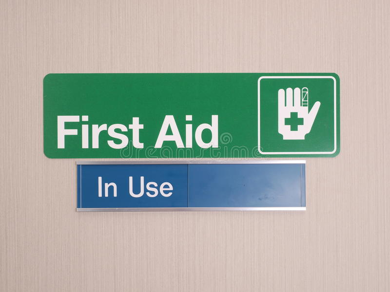 First aid door sign with occupied indicator stock photography