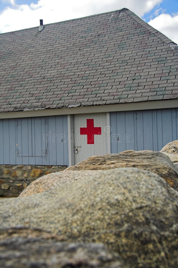 First aid hut. A beach hut with red cross symbol on a white door stock images