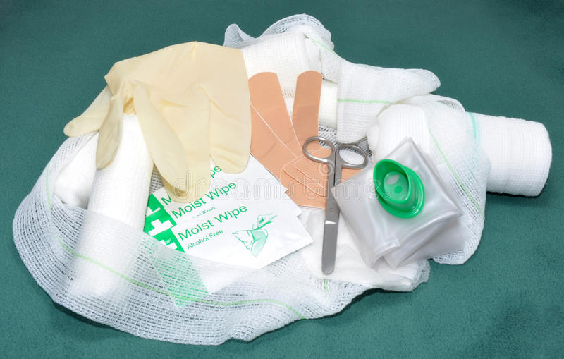 First Aid Kit Contents. Including open weave bandaged, plasters and scissors on a green fabric background stock images