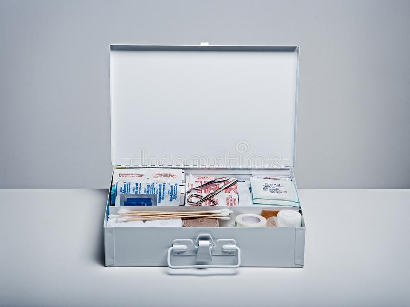 First aid kit packed with medical supplies on grey background. Organized first aid kit packed with emergency medical supplies on grey background stock images