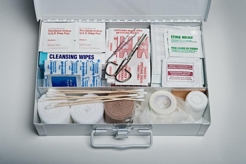 First aid kit packed with medical supplies on grey background. Organized first aid kit packed with emergency medical supplies on grey background royalty free stock image